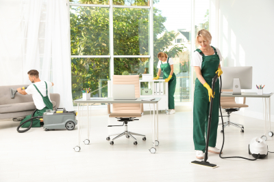 Team of janitors in uniform cleaning office