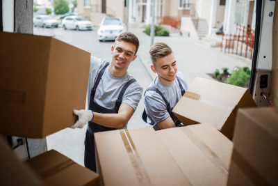Two young handsome smiling movers wearing uniforms are unloading